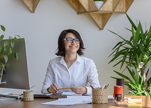 Happy desk worker with indoor plants on her desk